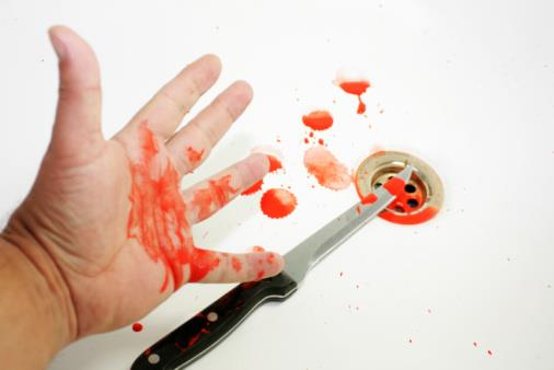 A bloodied hand over a bloodied knife set on a white background with blood splatters over a plug hole in a sink.