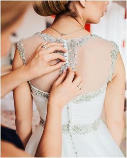 Помогает одеть свадебное платье