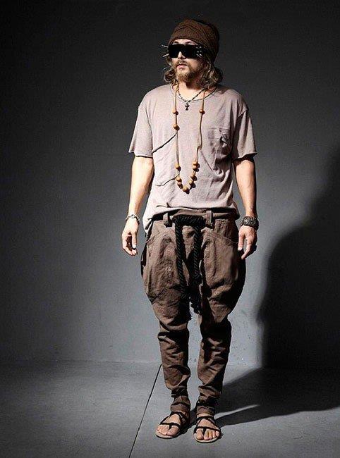Парень в стиле Бохо - штаны алибаба, серая футболка и стильные аксесуары