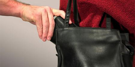 достает кошелек из черной сумки