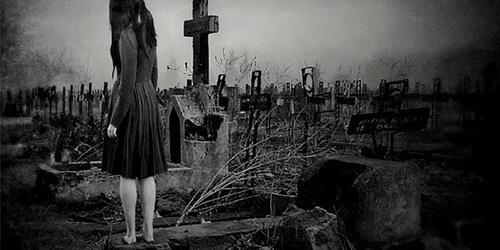 Девушка стоит на кладбище