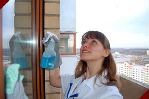 Девушка моет окна в своей квартире
