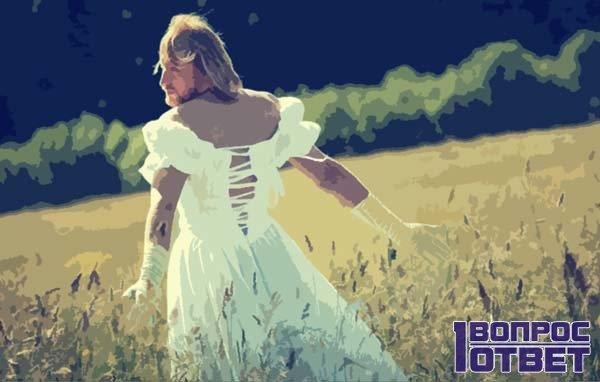 Мужчина на поле в свадебном платье