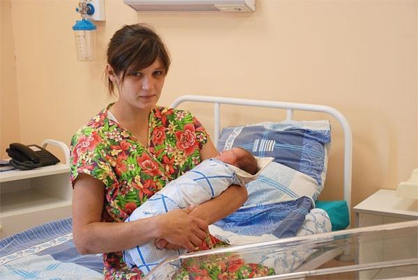 Мать держит новорожденную в роддоме